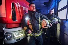 Two firemen wearing protective uniform standing next to a fire truck in a garage of a fire department. Two firemen wearing protective uniform standing next to a stock photos
