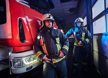 Two firemen wearing protective uniform standing next to a fire truck in a garage of a fire department. Two firemen wearing protective uniform standing next to a royalty free stock photo