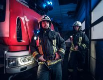 Two firemen wearing protective uniform standing next to a fire truck in a garage of a fire department. stock images