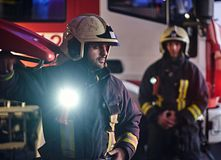 Two firemen wearing a protective uniform standing next to a fire truck. Arrival on call at night time royalty free stock photos