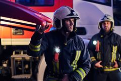 Two brave firemen wearing a protective uniform standing next to a fire truck. Arrival on call at night time stock photos