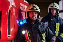 Two firemen wearing protective uniform standing next to a fire truck in a garage of a fire department. stock photo