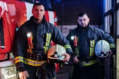 Two firemen wearing protective uniform standing next to a fire truck in a garage of a fire department. Two firemen wearing protective uniform standing next to a stock image