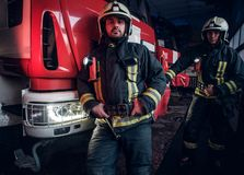Two firemen wearing protective uniform standing next to a fire truck in a garage of a fire department. Two firemen wearing protective uniform standing next to a royalty free stock image