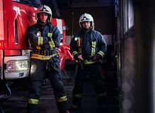 Two firemen wearing protective uniform standing next to a fire truck in a garage of a fire department. Two firemen wearing protective uniform standing next to a stock photography