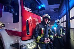 Two firemen wearing protective uniform standing next to a fire truck in a garage of a fire department. Two firemen wearing protective uniform standing next to a royalty free stock photos
