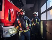 Two firemen wearing protective uniform standing next to a fire truck in a garage of a fire department. Two firemen wearing protective uniform standing next to a royalty free stock photography