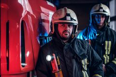Two firemen wearing protective uniform standing next to a fire truck in a garage of a fire department. royalty free stock images
