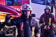 Two brave firemen wearing a protective uniform standing next to a fire truck. stock photo