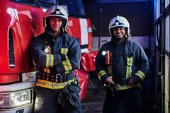 Two firemen wearing uniform standing next to a fire engine in a garage of a fire department, smiling and looking at a. Two firemen wearing protective uniform stock images