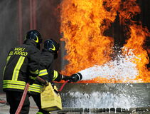 Two firemen who puts out the fire with a fire ex Royalty Free Stock Image