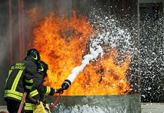 Two firemen who puts out the fire with a fire ex Royalty Free Stock Images