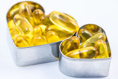 Two fish oil pill containers with pills in heart shape box  Royalty Free Stock Photography