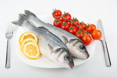 Two fish sea bass with lemon and tomato Stock Photography