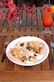 Two fish taco sandwichs served on plate. Two spicy fish tacos served on plate smothered in sauces. Portrait view with coctail and flower in the background Royalty Free Stock Images