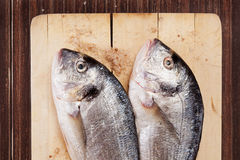 Two fish on wooden cutting board. Stock Photo