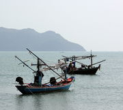 Two fisherboats. In the sea near Prachuab, Thailand. In the background is an island and another fisherboat Royalty Free Stock Image