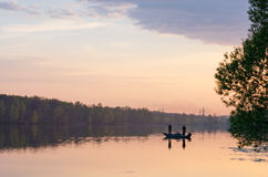 Two fisherman on boat at sunset Royalty Free Stock Photo
