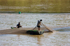 Two fisherman catching fish by net Stock Photos