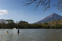 Two fisherman fishing in the shores of the Ometepe Island in Lake Nicaragua, with the Concepcion Volcano on the background Royalty Free Stock Photography