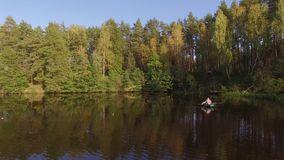 Two fisherman in rubber boat floats rowing with oars on river. Drone aerial shot. Man is fishing on lake in sunny forest. Stracha river - place close to stock video
