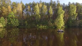 Two fisherman in rubber boat floats rowing with oars on river. Drone aerial shot. Man is fishing on lake in sunny forest. Stracha river - place close to stock video footage