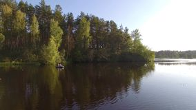 Two fisherman in rubber boat floats rowing with oars on river. Drone aerial shot. Man is fishing on lake in sunny forest. Stracha river - place close to stock footage