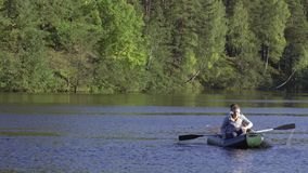 Two fisherman in rubber boat floats rowing with oars on river. Man is fishing on lake in sunny forest. Stracha river -. Beautiful place close to Belarusian stock video footage