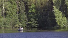 Two fisherman in rubber boat floats rowing with oars on river. Man is fishing on lake in sunny forest. Stracha river -. Beautiful place close to Belarusian stock video