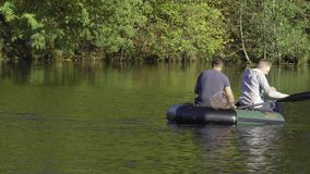 Two fisherman in rubber boat floats rowing with oars on river. Man is fishing on lake in sunny forest. Stracha river -. Beautiful place close to Belarusian stock footage