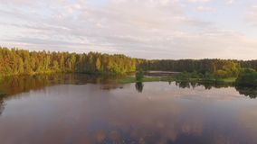 Two fisherman in rubber boat floats with white swan. Drone aerial shot. Friends relaxes in boat on lake in sunny forest. Stracha river, Belarus. Beautiful stock footage