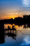 Two fisherman silhouette against sunset Stock Photos