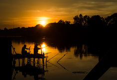 Two fisherman silhouette against sunset Royalty Free Stock Photography