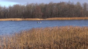 Two fishermans fishing in rubber boat on autumn lake water stock video