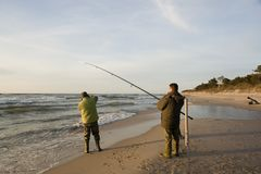 Two fishermen on beach Stock Photos