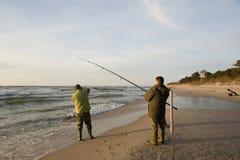 Two fishermen on beach stock photos