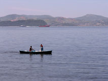 Two fishermen in boat. Two fisherman in small boat on ocean with coastline in background stock photos
