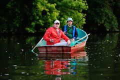 Two fishermen in a boat with fishing rods catching fish. Two fishermen in a red boat with oars with fishing rods catching fish on the background of the river and Royalty Free Stock Photo