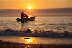 Two fishermen on a boat fishing on a sea with beautiful sunrise. In background royalty free stock image