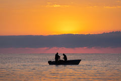 Two fishermen on a boat fishing on a sea with beautiful sunrise. In background royalty free stock images