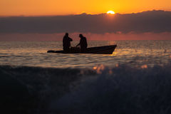 Two fishermen on a boat fishing on a sea with beautiful sunrise. In background royalty free stock photo