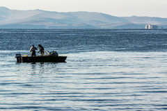 Two fishermen in a boat on the lake Royalty Free Stock Photos