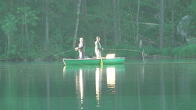 Two Fishermen in a Boat on Morning Forest Lake. Editorial Use Only. Germany, Hintersee Lake. Forest lake early in the morning. Windless sunny weather. Two stock footage