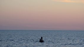 Two fishermen on the boat throw the net into the sea at sunset sky background.  stock footage