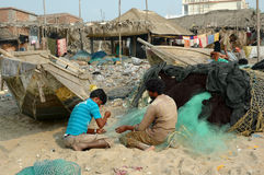Two fishermen busy mending nets in Puri, Orissa, India. Royalty Free Stock Photos