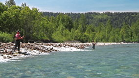 Two fishermen. Casting fly fishing at a mountain river stock video footage