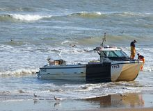 Fishermen climbing from boat on the beach. royalty free stock image