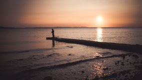 Two fishermen at the cost during sunset. Royalty Free Stock Photos