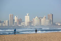 Two Fishermen on Durban Beach with Hotels in Background Royalty Free Stock Photos