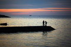 Two fishermen fish at sunset on the Black Sea Royalty Free Stock Image